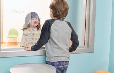 A glass-walled room allows patients to chat face to face with siblings without fear of infection.