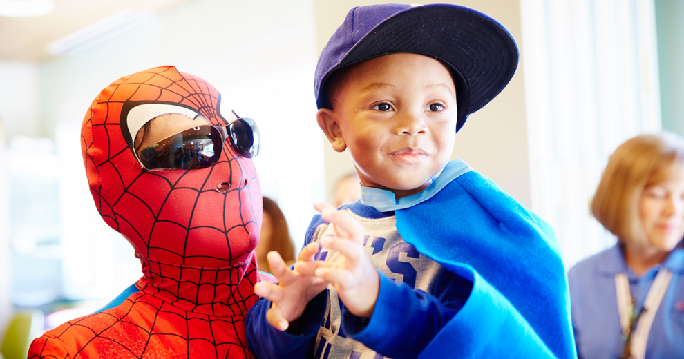 Spiderman holding little boy