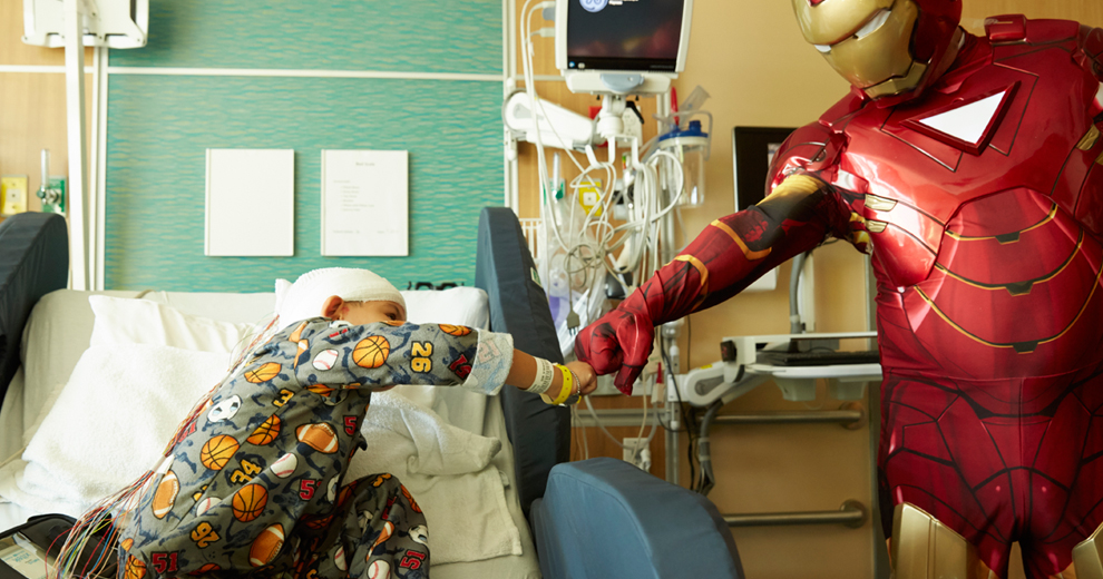 Little boy bumping fists with Iron Man