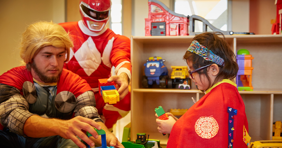 Superheroes playing blocks with little girl